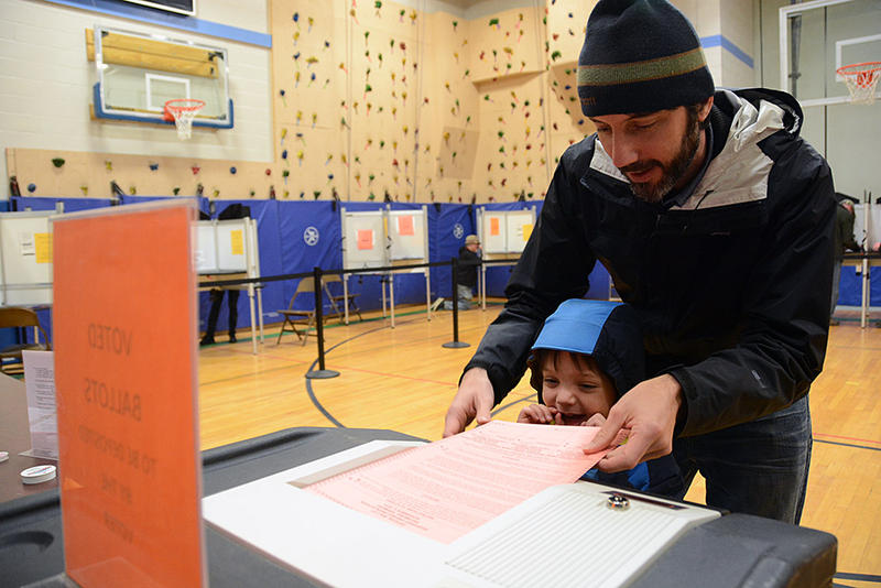 Miles Witters, 4, of Richmond, helps his dad, Sean, submit a ballot at Camel's Hump Elementary School on Tuesday morning.