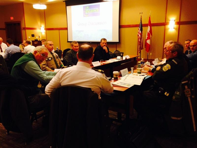 Officers from Canada and Vermont trade suggestions about cross-border cooperation at a conference at Jay Peak resort.