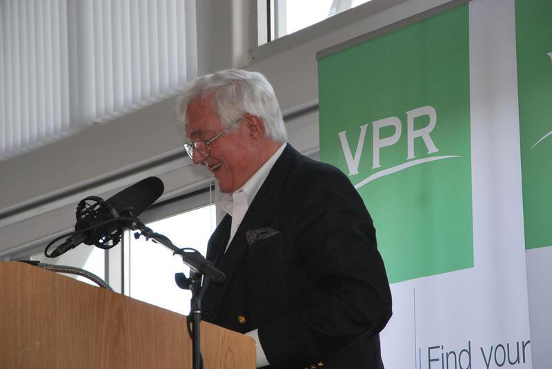 Barrie Dunsmore speaks at a podrum with a VPR sign behind him at a VPR's 2014 commentator brunch.