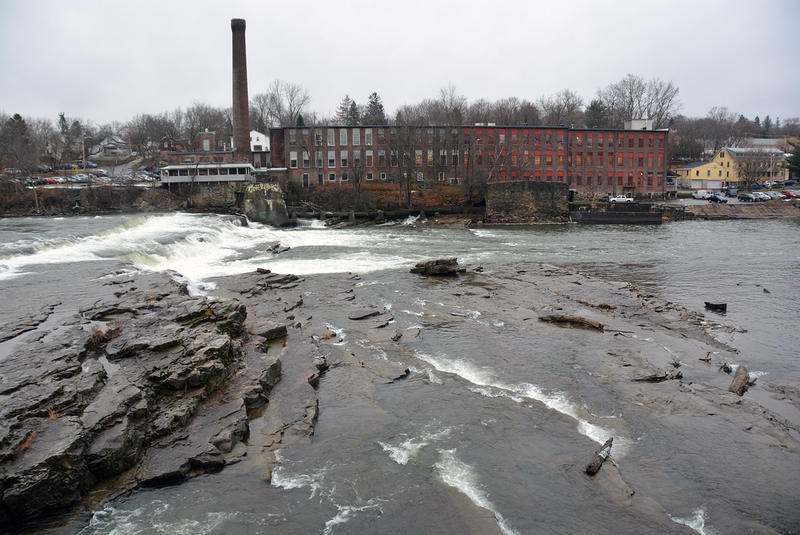 Looking over the Winooski River to a building on a cloudy day.
