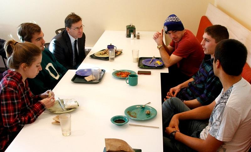 Professor Charles Wheelan (upper left) discusses the diplomatic thaw with Cuba at lunch with students in a Dartmouth Dining Hall. The College is planning to establish an exchange program with Cuba next fall.