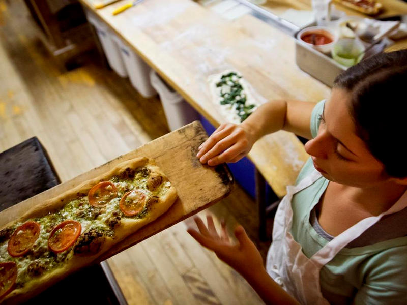 "Kim Rich checks on a tomato pesto pizza at Barrio Bakery on North Winooski Avenue in Burlington. This is one of the many places to enjoy ""cheap eats"" in the Burlington area."