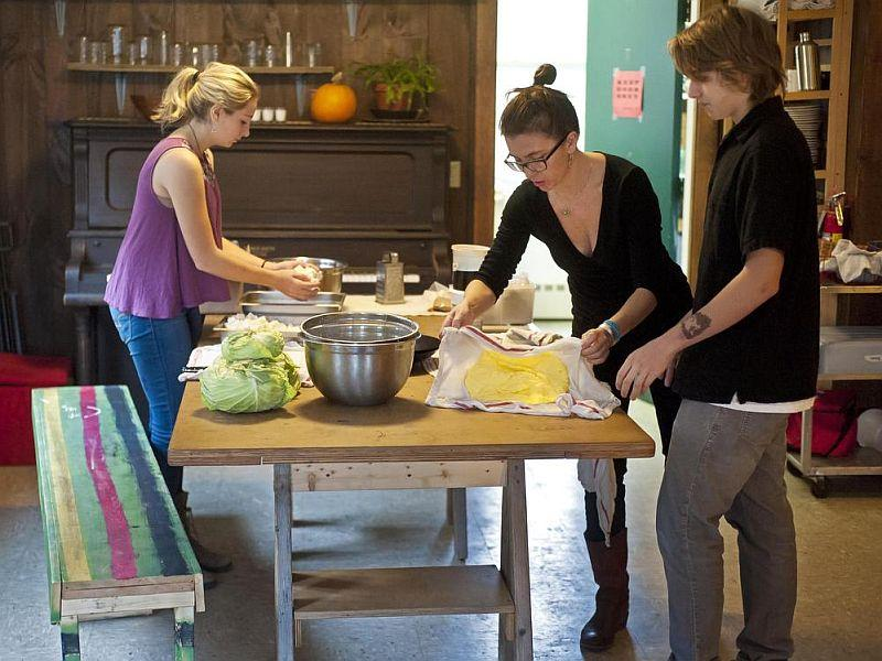 Crystal Madiera shows 11th grader Enoch Marshall of Saint Johnsbury (right) how to knead water out of butter. Isabelle Taylor (left) prepares a spicey tofu and cabbage salad.