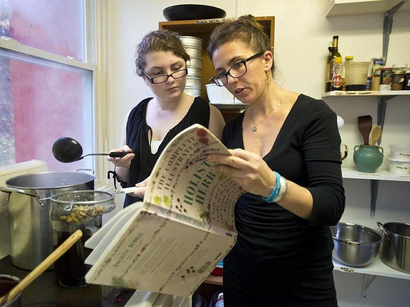 Crystal Madeira (right) explains the properties of herbs that Alexa West, an 11th grader from East Montpelier, is using to make chai.