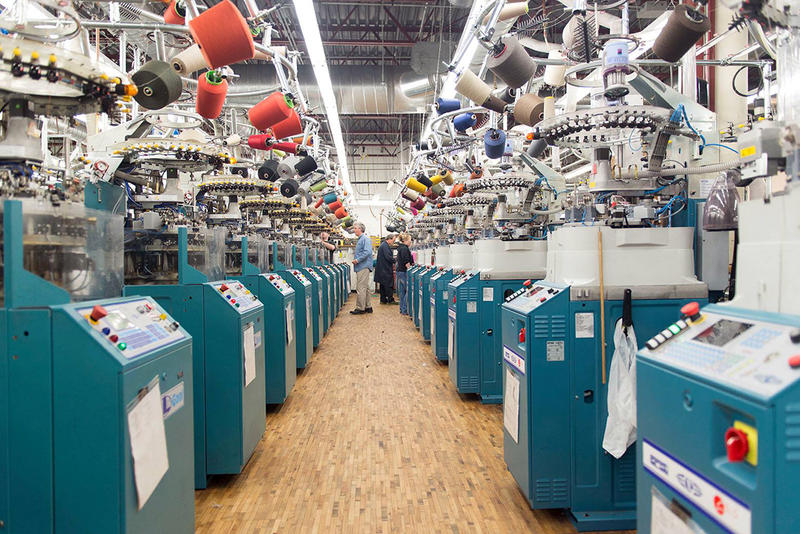 Colored thread hangs above a knitting aisle at the Darn Tough mill in Northfield. The company is planning an expansion that will nearly double the size of its facility and add approximately 50 jobs in the Northfield area.