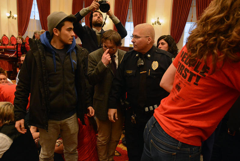 A protester and an officer shared a tense moment after law enforcement prevented the group from holding up a banner in the middle of the House floor after most lawmakers and observers had left.