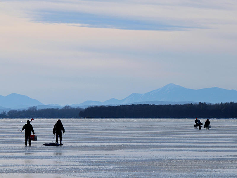 Ice fishing enthusiasts walk on Lake Champlain ice south of Sandbar State Park in Milton in January 2012. Fisherman often eat the delicious trout, salmon or walleye that they've caught in the lake.