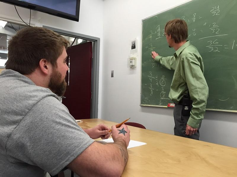 Tim Colby takes a math class from Nick Rulon at the Northeast Correctional Complex in St. Johnsbury. A proposal to drastically cut funding for the program has both inmates and instructors worried.