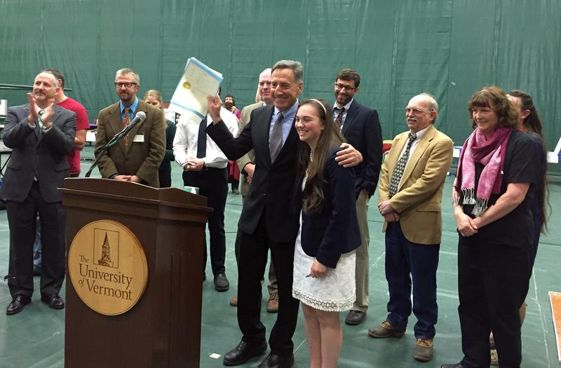 Gov. Peter Shumlin holds up the bill that creates Vermont's new Latin motto. He's joined by ninth-grader Angela Kubicke, who composed the motto.