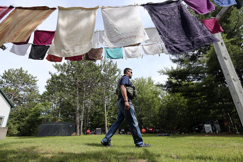 An officer walks through a backyard in Cadyville, New York on June 14 as the search for Richard Matt and David Sweat, convicted murders who escaped from Clinton Correctional Facility in nearby Dannemora, continues.