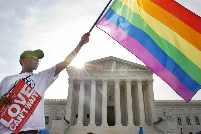 Carlos McKnight of Washington waves a flag in support of gay marriage outside of the Supreme Court in Washington on June 26. The court has passed down a decision that legalizes same-sex marriage in all 50 states.