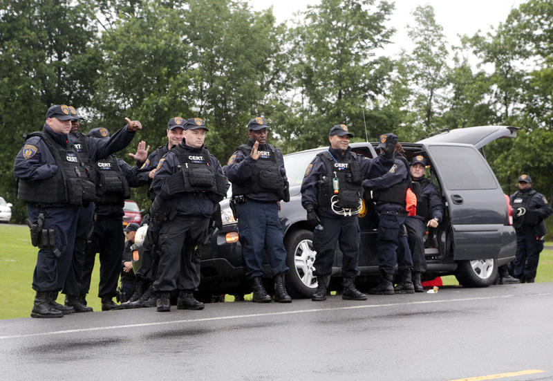 Corrections officers wave to passing motorists who cheered them after the second of two escaped prisoners was apprehended on Sunday, June 28 in Constable, N.Y. David Sweat was shot and taken into custody on Sunday; Richard Matt was killed on Friday.