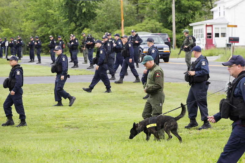 Teams of corrections officers and a police dog walk across a field towards woods near the Clinton Correctional Facility in Dannemora, New York on June 16. The manhunt has thusfar been successful, and authorities have recently begun scaling it back.