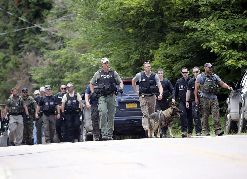 Law enforcement officers in search of David Sweat and Richard Matt walk along a road in Owls Head, N.Y. on Monday. New York State Police have found items in a seasonal hunting cabin that could be connected to the inmates.