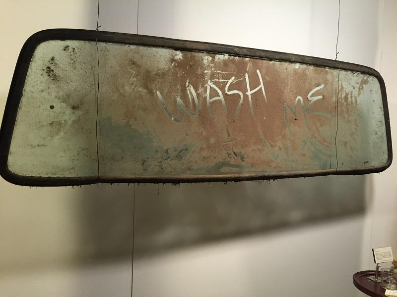 "A windshield covered in mud sits on display at the Everyday Life Museum in Glover. It's part of an exhibit called ""Dust"" which explores the idea of dust and dirt in various ways."