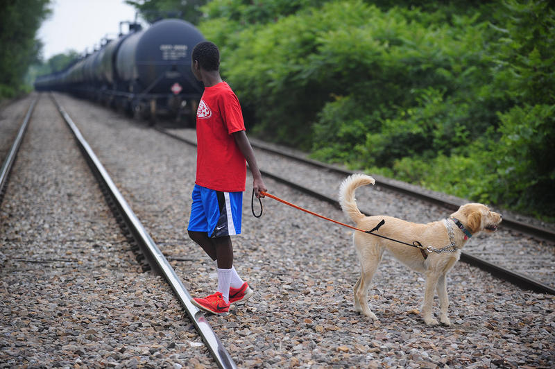 Nani Clemmons, 13, uses an agricultural crossing of rail lines near his home in Charlotte. Behind him, a long line of petroleum tank cars sits on an unused side track. Residents are concerned about the storage of explosive materials in their town.