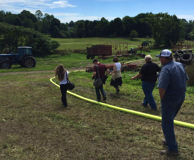 A yellow hose carries manure to a hay field during a demonstration of drag-line spreading at Vermont Technical College in Randolph.