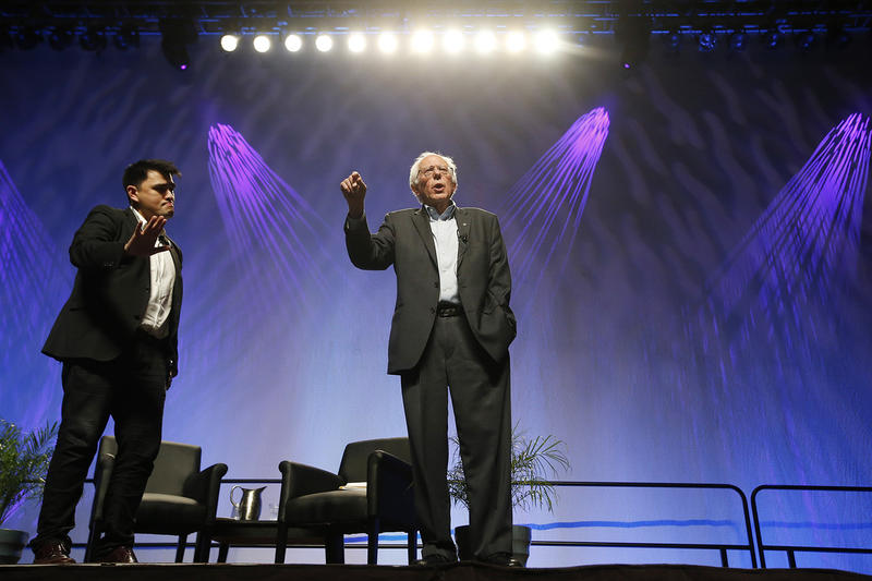 Sen. Bernie Sanders tries to speak as he is shouted down by protesters as moderator Jose Vargas, left, tries to quiet the protesters in the crowd at a Netroots Nation town hall meeting on July 18 in Phoenix.