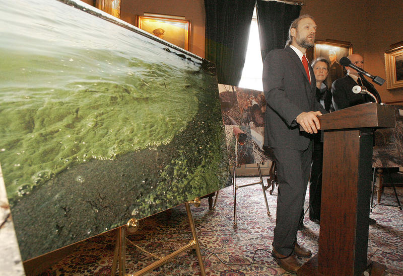 A photo showing an algae bloom in Lake Champlain is displayed as Christopher Kilian, left, of the Conservation Law Foundation, speaks at a news conference in this 2009 file photo.
