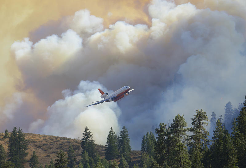 A tanker airplane flies in front of billowing smoke after making a fire retardant drop near Twisp, Wash., on Aug. 21. Massive wildfires across the state and region have overtaxed firefighters, and some Vermont crews have traveled out to lend a hand.