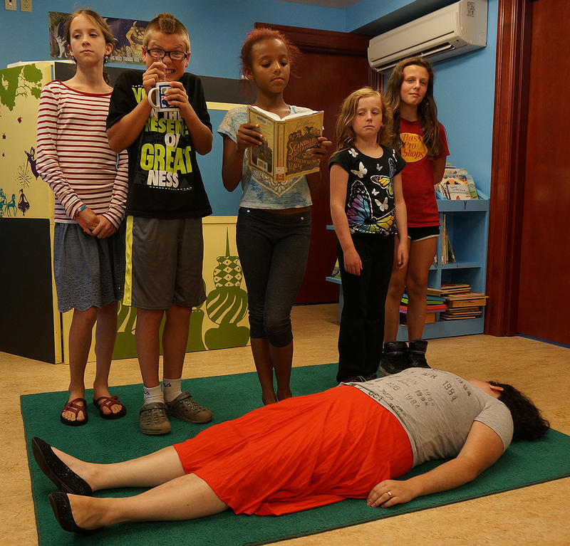 Summer readers at Morristown Centennial Library reenact the cover of the book 'The Scandalous Sisterhood of Prickwillow Place'.