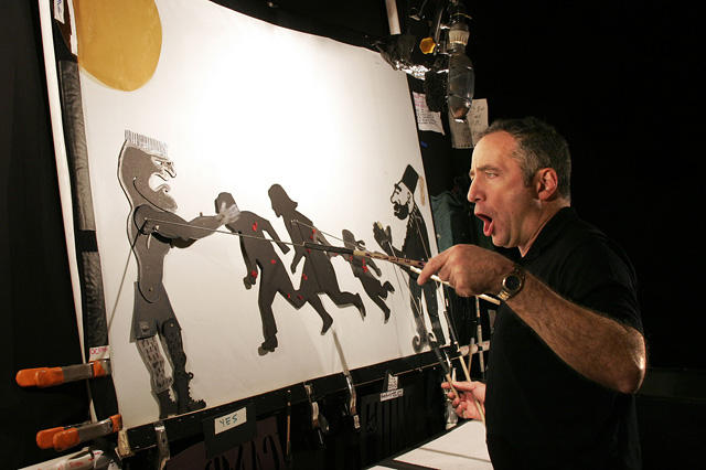 "Zaloom performs with shadow puppets in a backstage view from ""The Mother of All Enemies."" (File photo)"