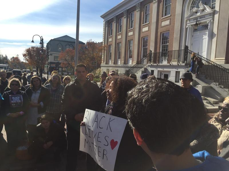 "Vicki Garrison holds up a ""Black Lives Matter"" sign at a press conference in front of Burlington's City Hall."