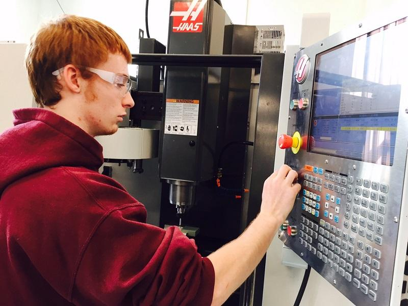 Zebadiah Updike, an engineering student at Vermont Technical College, programs a drill press that can make three-dimensional objects, following student-generated computer codes.
