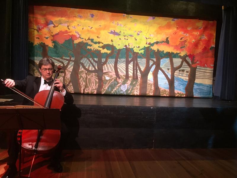 "John Dunlop, of the Vermont Symphony Orchestra, perfroms in front of the curtain, ""Autumn,"" painted by Michele Ratte."