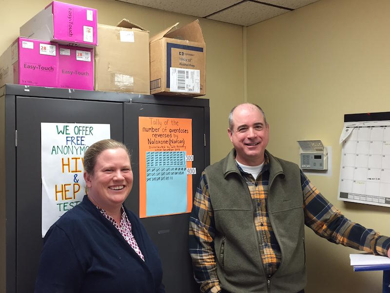 Grace Keller, left, and Tom Dalton, right, are the last two staff members at the Safe Recovery Program. The poster behind them keeps a tally of the potential deaths averted by overdose-reversal kits handed out by the program.