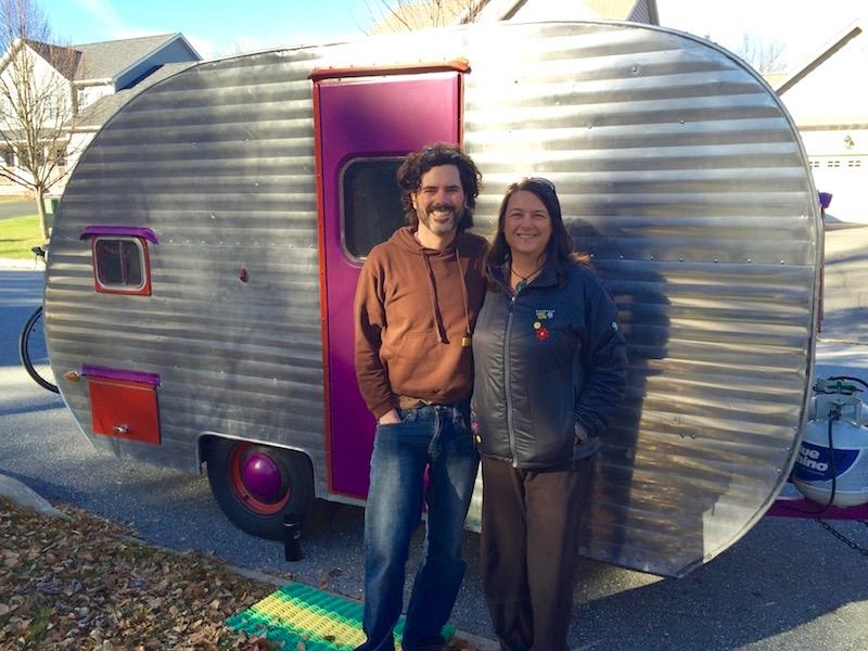 Dave Hutchison and Shari Galiardi in front of their tiny home: a refurbished 1957 chrome camper trailer.