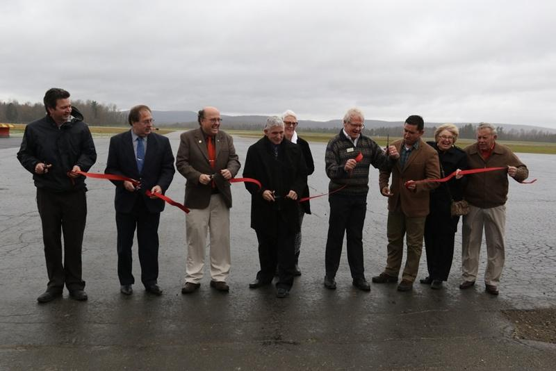 A group of officials, including Vermont Aviation Administtrator Guy Rouelle and Northeast Kingdom developer Bill Stenger, cut the ribbon at the entrance to an expanded runway at the newly re-named Northeast Kingdom International Airport in Coventry.