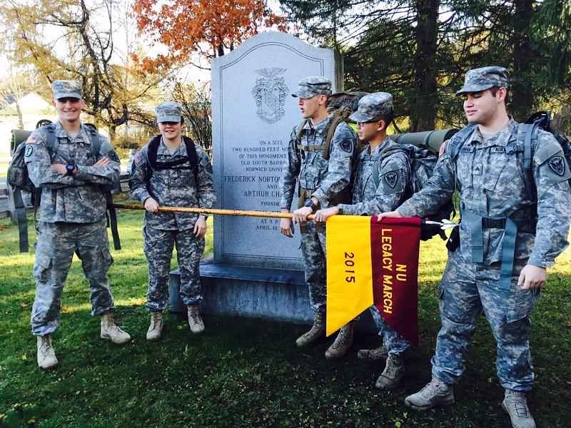 Norwich cadets Jacob Jahr, Kelly Lincoln, Nolan Ferguson, Kyle Bvu and James Dallas Gibbon pose at a monument to their college history on the town green in Norwich.