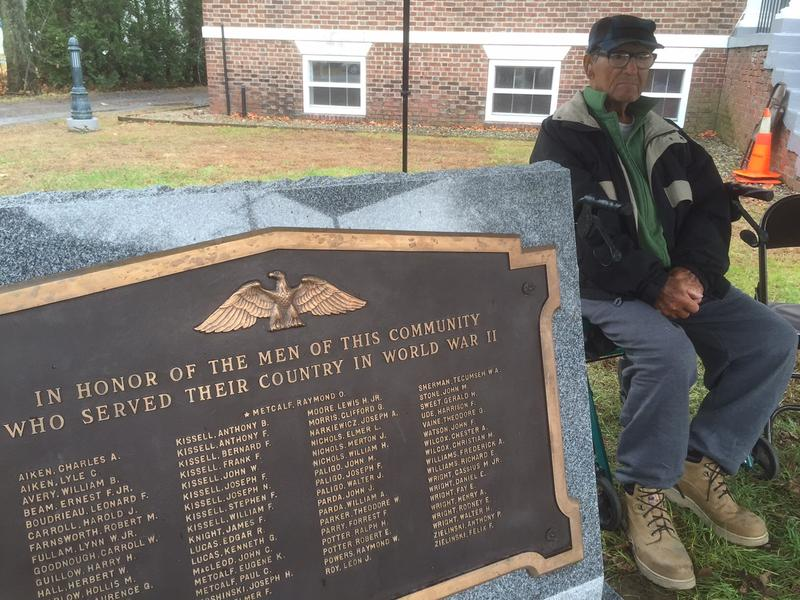 Artie Aiken sits behind the granite World War II monument he helped bring to Westminster.