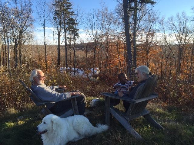Nancy Tips, far right, plays with her grandson, Fred, while her husband Frank Seawright looks on. The ridge where a controversial 28-turbine wind project would be built is in the distance.
