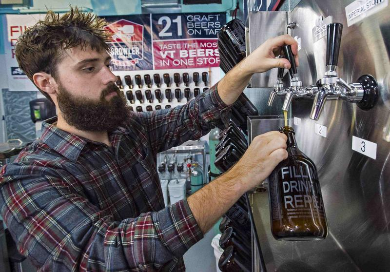 Tyler Delisle fills a growler with a mango IPA at the Growler Garage in South Burlington.