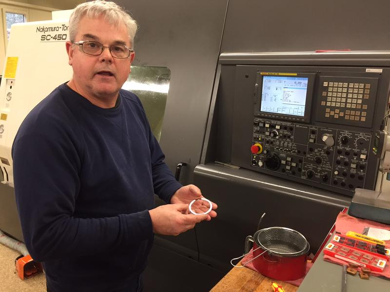 David Gordon shows a precision washer as he works at a computerized-numerically controlled lathe at G.S. Precision.