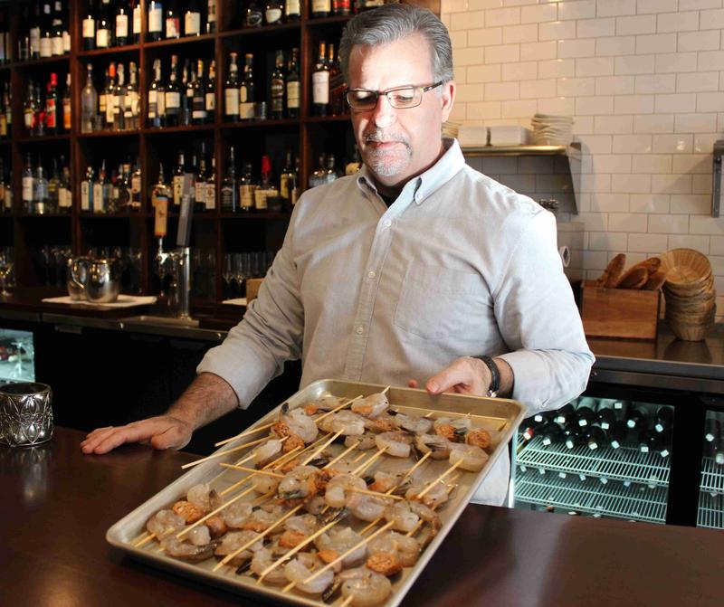 Kevin Cleary, chef and co-owner of Vin Bar and Shop shows off a tray of garlicky shrimp and chorizo on a skewer.