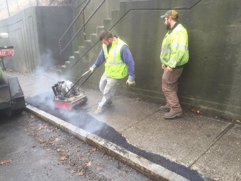 Brattleboro Public Works employee Brian Frechette, left, pulls a compactor over hot asphalt as Scott Johnson looks on.