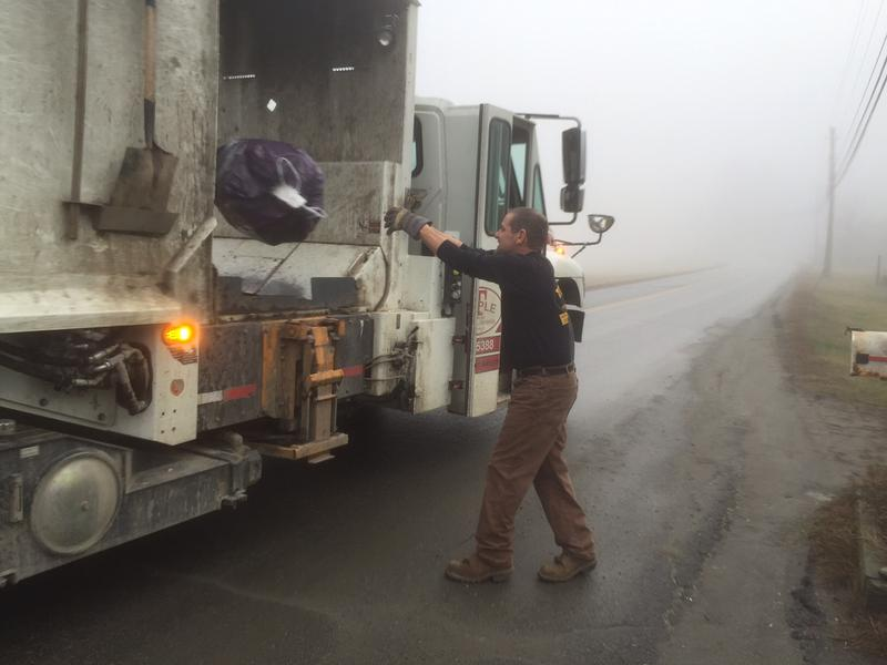 Andre Smith tosses a pay-as-you-throw garbage bag into his truck while on his route in Brattleboro. The town's early adoption of practices that will be mandatory under Vermont's new universal recycling law are already reducing waste and saving money.