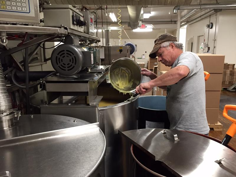 Jeff Aldrich pours warm bag balm into a machine that will fill newly sized tins at the Lyndonville Factory.