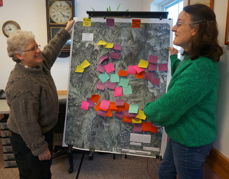 Bolton Planning Commissioner Deb Shelby (left) and Assistant Town Clerk Carol Devlin take a look at a town map where residents, including elementary school students, have posted planning priorities and comments.