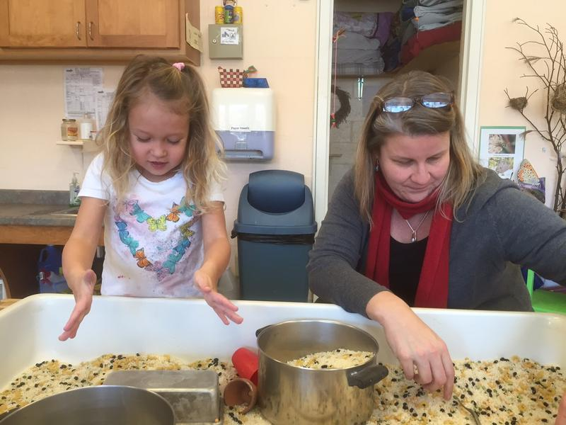 Ava Keppler, 5, makes a cake in a grain and corn box while Winston Prouty Center Executive Director Chloe Learey lends a hand. The center expects to move into the space formerly occupied by the Austine School in June.