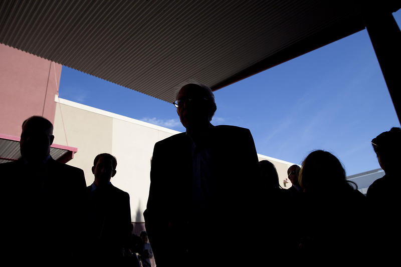 Sen. Bernie Sanders, center, is silhouetted as he talks to voters at a caucus site on Feb. 20 in Las Vegas. Several respondents to the VPR Poll cite candidates' composure, experience, honesty and personal integrity as factors determining their support.