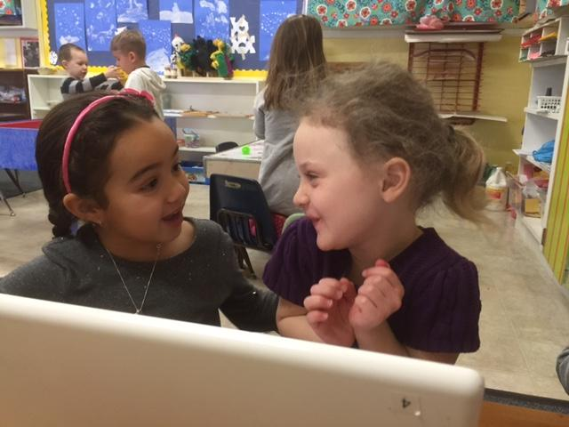 Madden Gholston, left, helps Autumn Lesley work at a computer at Tinmouth Elementary School. On Town Meeting Day, Tinmouth will vote on merging with three other towns to form one school district.