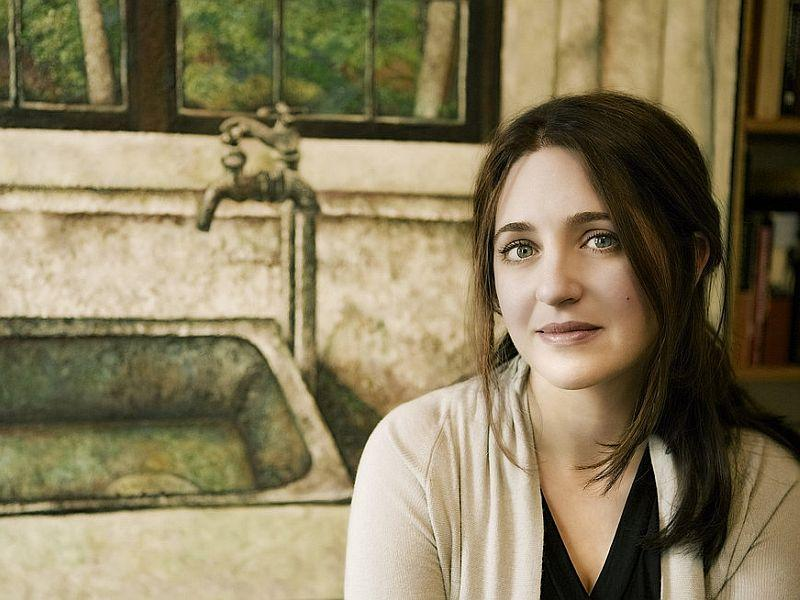 Simone Dinnerstein posing in front of one of her father's paintings.