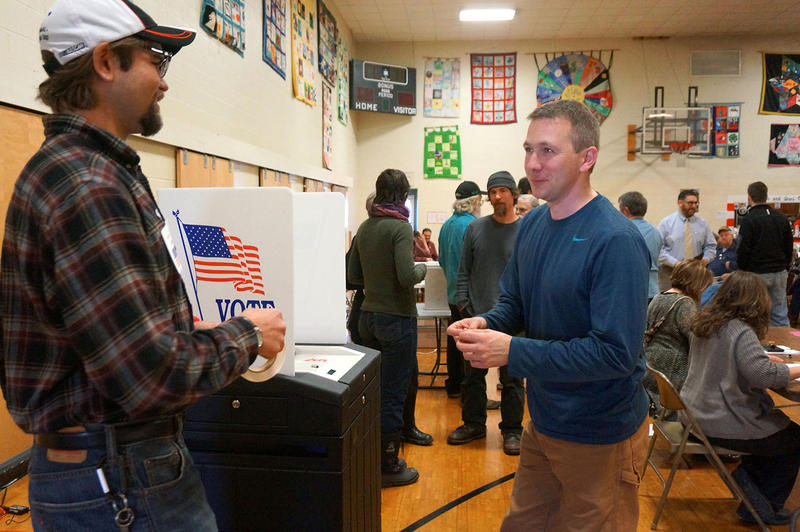 "Wolcott election official Joe Slaimen gives an ""I voted"" sticker to voter Ryan Bjerke."