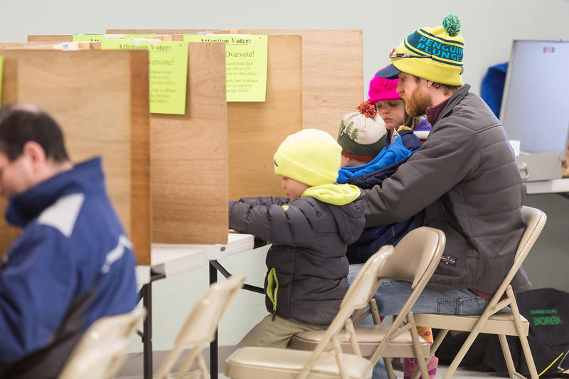 Burlington resident Geoff Bennett votes with his children at the Robert Miller Recreation Center polling location on Tuesday morning.