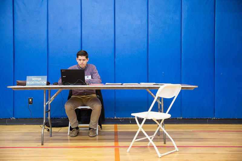 Voter registration assistant Alex Farrell works the Burlington Ward 6 polling location at Edmunds Middle School on Tuesday morning for Town Meeting Day.