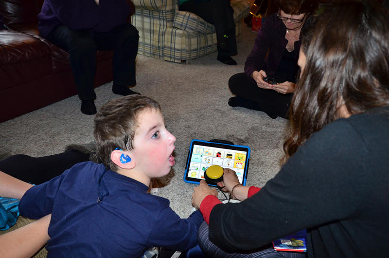 Five-year-old Anthony Arguin works with Amy Starble, of UVM's I-Team, on an augmentative communication device. Devices such as this one help non-verbal children and adults express themselves.